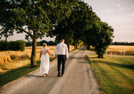 bride and groom walking hand in hand at Sywell Grange wedding venue