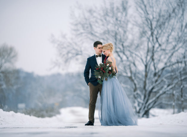 wedding day - Bride and groom among snowy landscape.